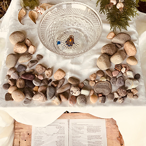 Stones, text, glass bowl and hamsa at one of the community-generated sacred spaces for 5781.