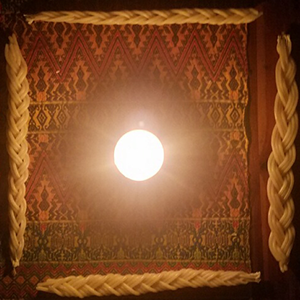Four braided candles arranged in a square against a red tapestry background, with a single bright, lit tealight in the center.