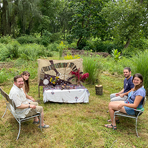Image shows four people sitting on two benches on either side of a table, in a landscape of grass, flowering plants and trees. The table has a cloth covering and small objects such as candles and pinecones. Behind the table is a cloth banner that includes the word TZEDAKAH in Hebrew and an attached Nishmat Shoom logo.